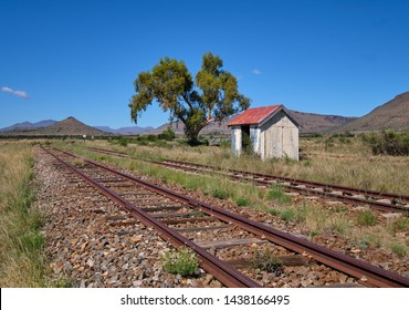 No longer in usage Dwarsfeld train station  in the Karoo region of South Africa. View of station and tracks leading to mountains. End of wet season, so still some green