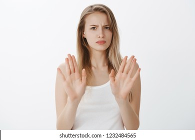 No meant not. Portrait of intense displeased and uninterested charming young blonde with moles in white top raising hands and waving in no and rejection gesture, frowning from dislike, refusing