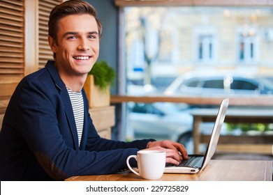 No minute without my laptop. Handsome young man working on laptop and smiling while enjoying coffee in cafe