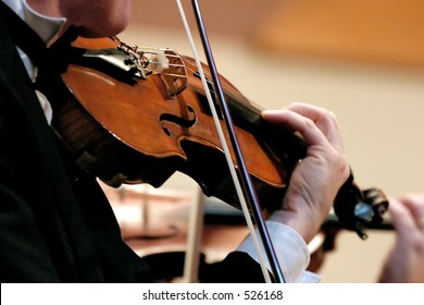 No Model here.  Closeup of musician playing the violin during a symphony - soft fous