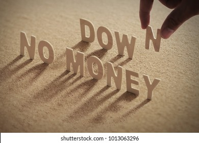 NO MONEY DOWN wood word on compressed or corkboard with human's finger at N letter.