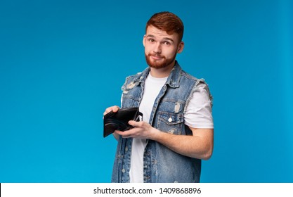 No money for living. Sad millennial man showing his empty wallet to camera on blue background, copy space