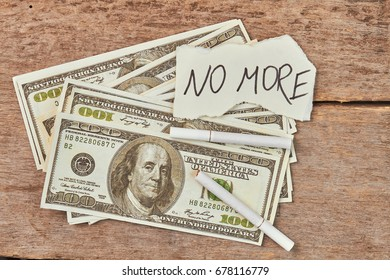 No more cigarette smoking concept. Dollars, cigarettes, message no more, wooden background.