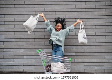 No more plastic. African woman with shopping cart trolley and eco bags jump outdoor market.