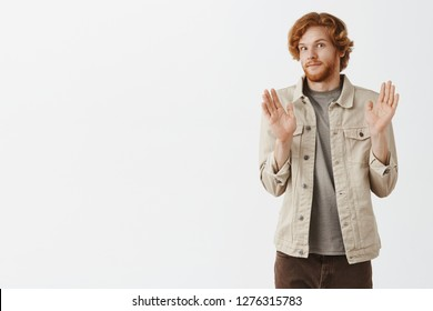 No offence sorry pal. Portrait of intense redhead male with beard feeling awkward smiling tight from discomfort raising palms in surrender and turning away from camera refusing or apologizing
