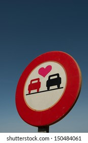 A no overtaking road sign with a love heart