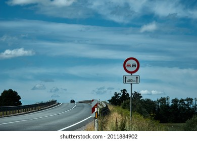 No overtaking sign. Road sign on the road in front of the bridge against the blue cloudy sky . High quality photo