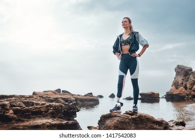 No pain, no gain. Confident disabled woman in sportswear with bionic leg standing on a stone in front of the sea and thinking about life goals.