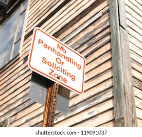 no panhandling or soliciting zone sign near wooden building