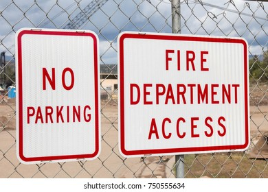 No Parking and Fire Department Access signs on a chain link fence surrounding a construction site