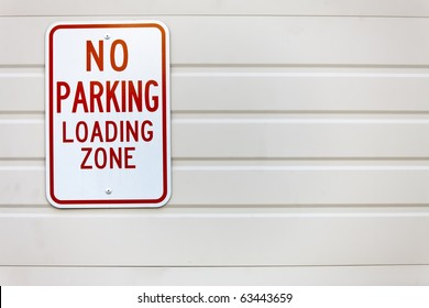 A no parking loading zone sign against a building