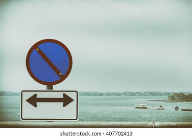 No parking sign and another sign of compulsory direction with the sea and sky background vintage style