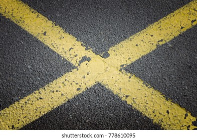 No parking sign. Asphalt texture with yellow crossed lines on the street.