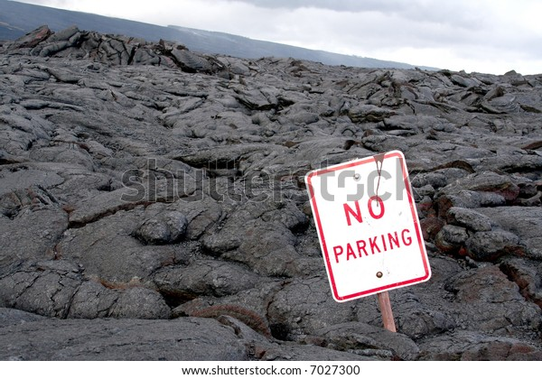 """A """"No Parking"""" sign found in a dried up field of lava."""
