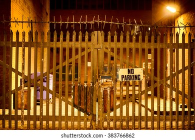 No Parking Sign on Gate at Night Time.
