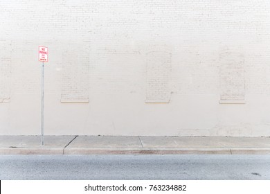 No parking sign on a street next to distressed white brick wall in urban downtown area.