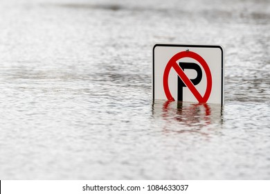 A No Parking sign in water. Water completely covers the signpost and partially covers the sign. Closeup view.