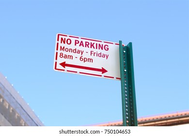 NO PARKING street sign, applicable daytime on week days, stands against a blue sky