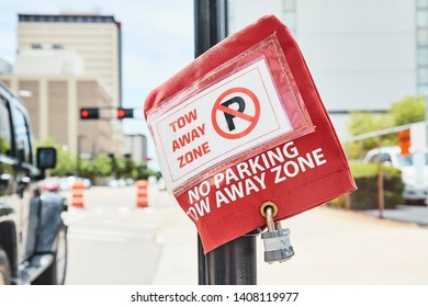 A No Parking and Tow Away  Zone warning in a downtown city on a bright sunny day.