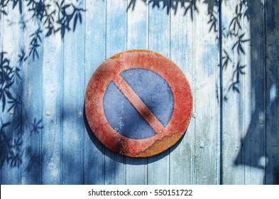 no parking traffic sign on a blue wooden garage door