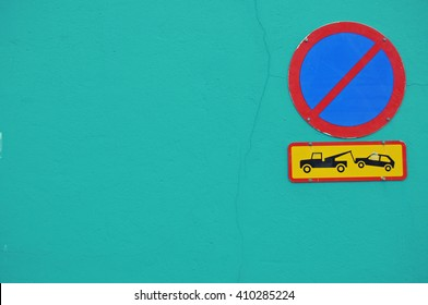 No parking traffic sign with a threat of towing away, on a turquoise wall