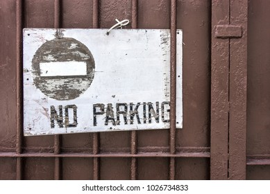 No parking vintage plate on the metal fence