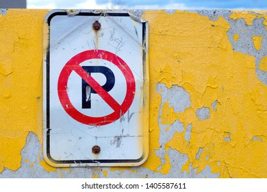 no parking warning old sign yellow paint concrete