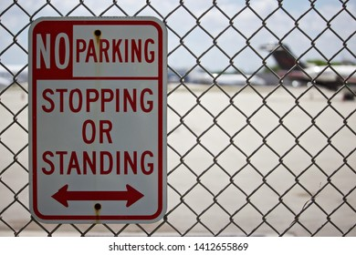 No parking,stopping,or standing sign with bi-directional arrow, with intentionally out of focus aircraft in background