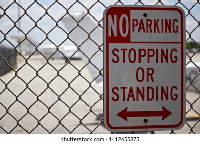 No parking,stopping,or standing sign with bi-directional arrow,with intentionally out of focus aircraft in background