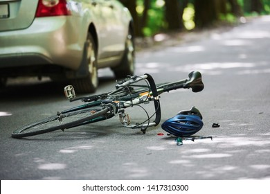 No people. Bicycle and silver colored car accident on the road at forest at daytime.