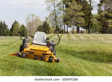 No person on expansive lawn with a yellow zero-turn mower