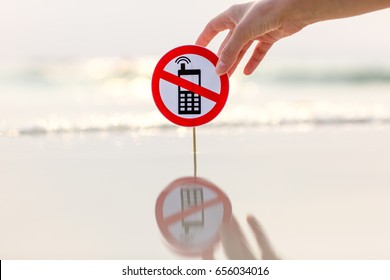 """No phone calls"" sign held by female hand on the beach on sea background"