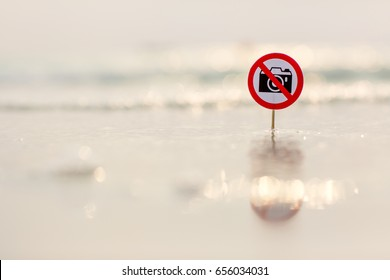 """No photo"" sign on the beach on sea background"