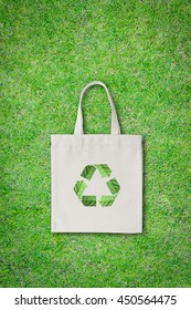 No plastic bag, shopping bag concept with fabric sack cloth totebag with recycle sign isolated on green lawn (clipping path)