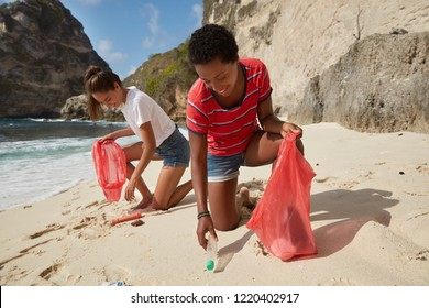 No plastic concept. Two interracial young women pick up garbage in litter bags from beach, clean seashore, protect environment from pollution, try prevent ecological disaster, do volunteer work