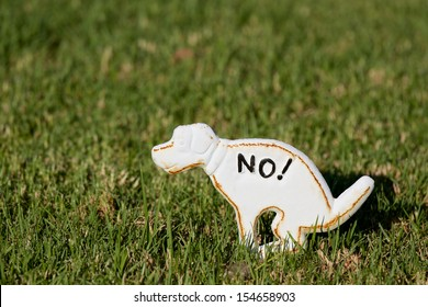 No pooping on the grass sign, shaped like a dog.