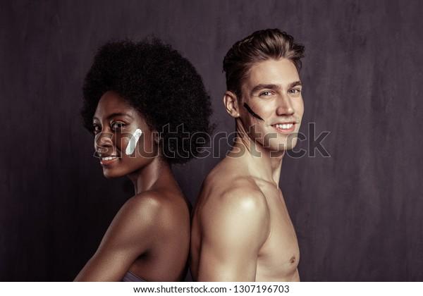 No prejudices. Joyful international couple smiling while standing together