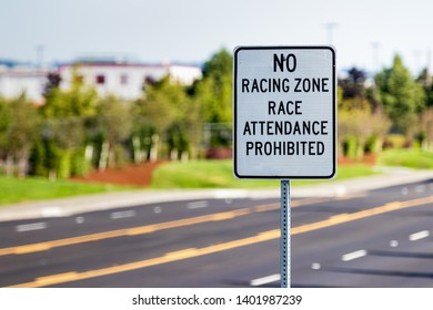 No racing zone sign on a post with a street