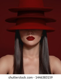 No recognizible model with half of a face covered by red hats and wear a strong matte red lipstick. Red background. image about red lips
