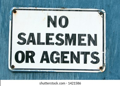 """A """"No Salesmen"""" sign on an aged blue background."""