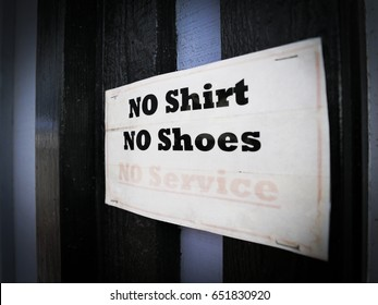 No shirt, No shoes, No services Sign on the glass wall with light and shadow