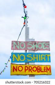 """""""No shoes, no shirt, no problem"""" sign on the beach"""