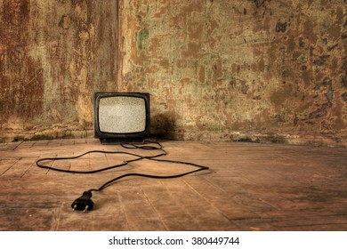 No Signal. An old TV with the noise on its display standing on the dirty floor
