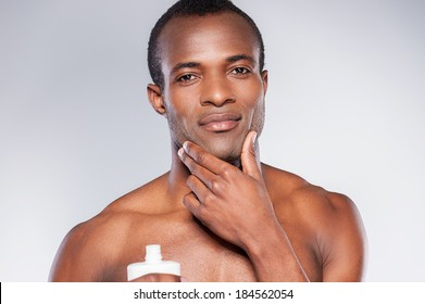 No skin irritation. Young shirtless African man applying cream at his face and looking at camera while standing against grey background
