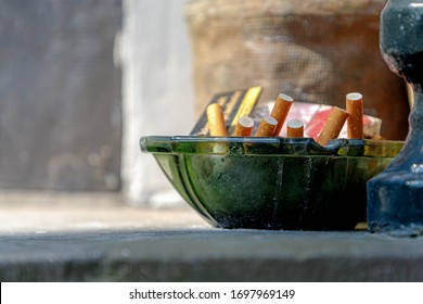 No smoking day concept, Selective focus of cigarette filter butts in green glass ashtray, Outdoor cigarette ashtray full with many bottoms of tobacco.