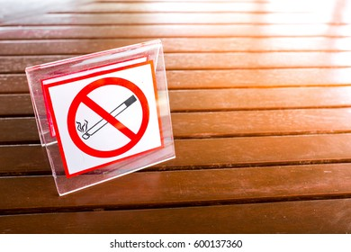 No smoking sign on the table. To remind you to smoke in this area. With the light coming from the side.