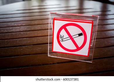 No smoking sign on the table. To remind you to smoke in this area. With the vignette light.