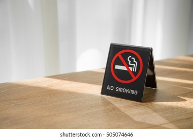 No smoking sign on wooden table in hotel room