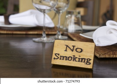 no smoking sign in restaurant, hand paint on natural wood with copyspace on left
