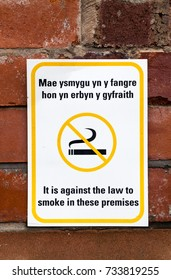 No Smoking Sign, Yellow and white signage with the words It is against the law to smoke on these premises,